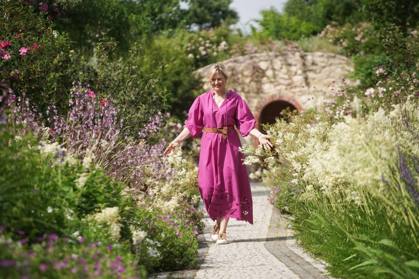 Maja Popielarska (Maja w ogrodzie) spaceruje po ogrodzie w fioletowej sukience.