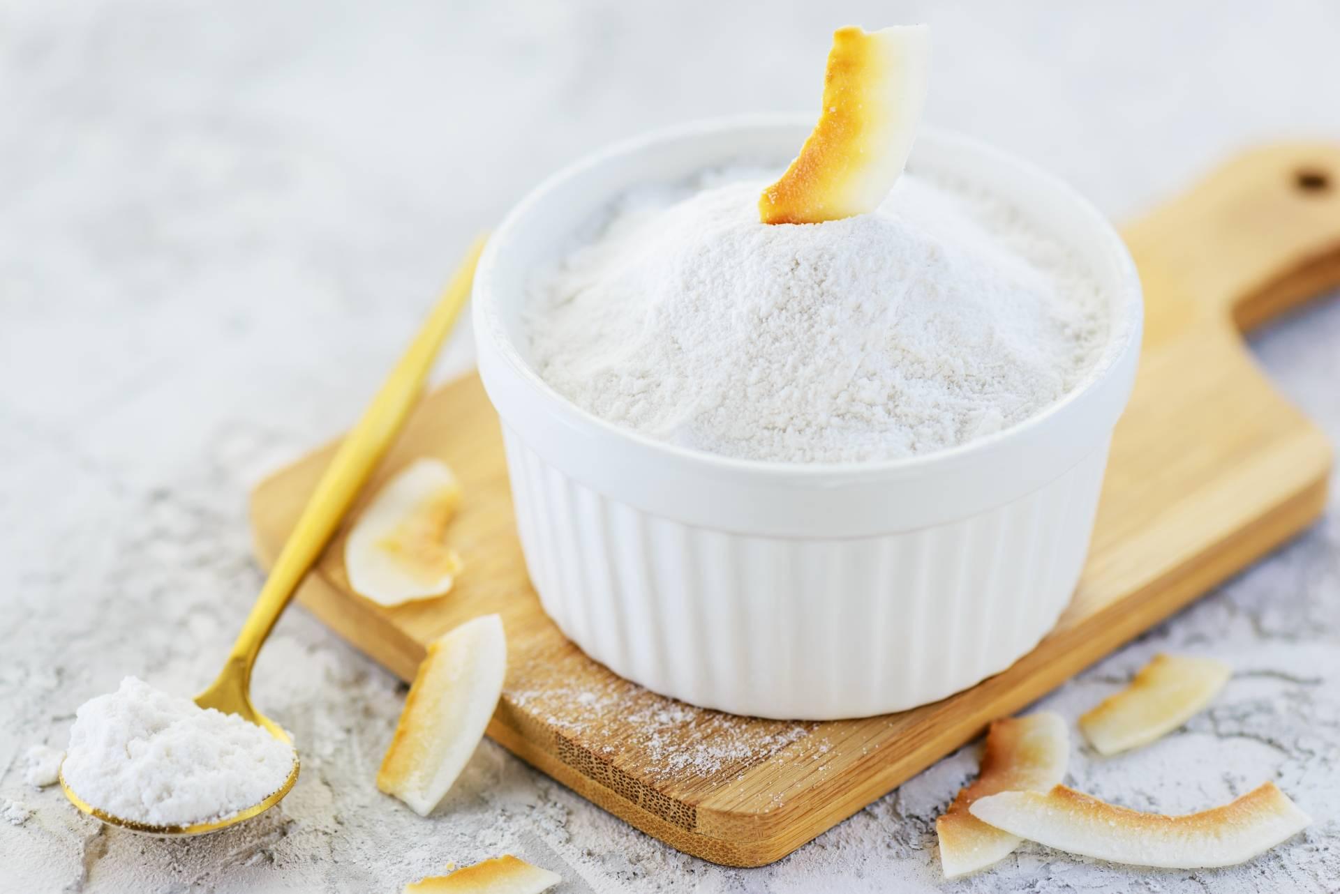 Mąka kokosowa w białej miseczce z kawałkami kokosa na drewnianej desce do krojenia.