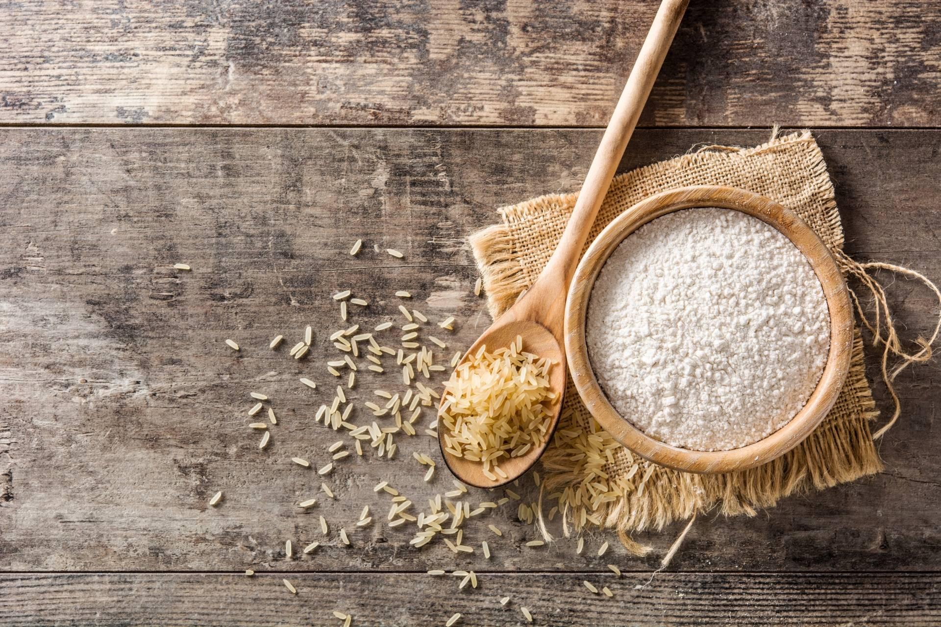 Mąka ryżowa w drewnianej miseczce na drewnianym blacie. Mąki bezglutenowe.
