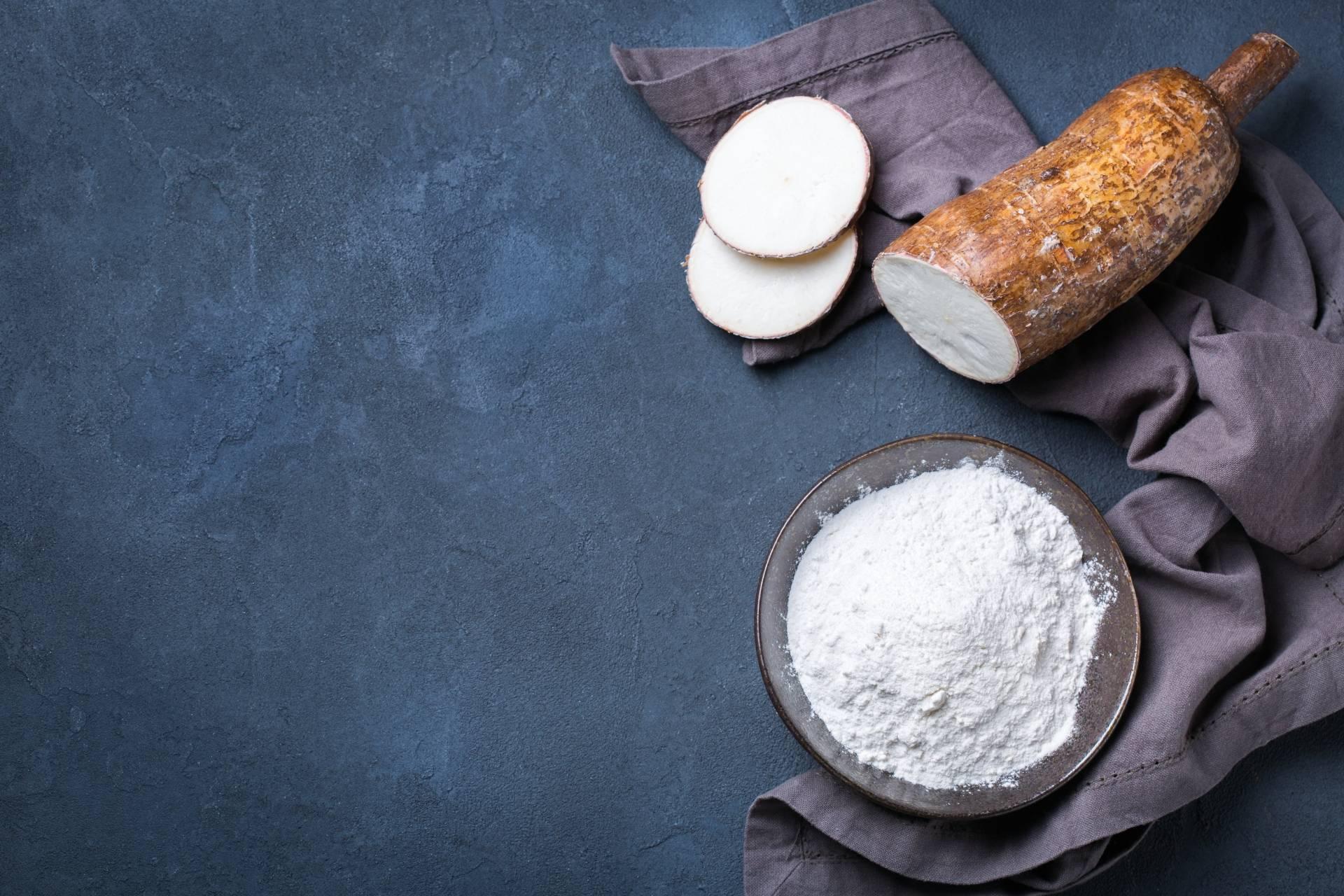 Mąka z tapioki w miseczce, obok leży maniok. Kompozycja na granatowym tle.