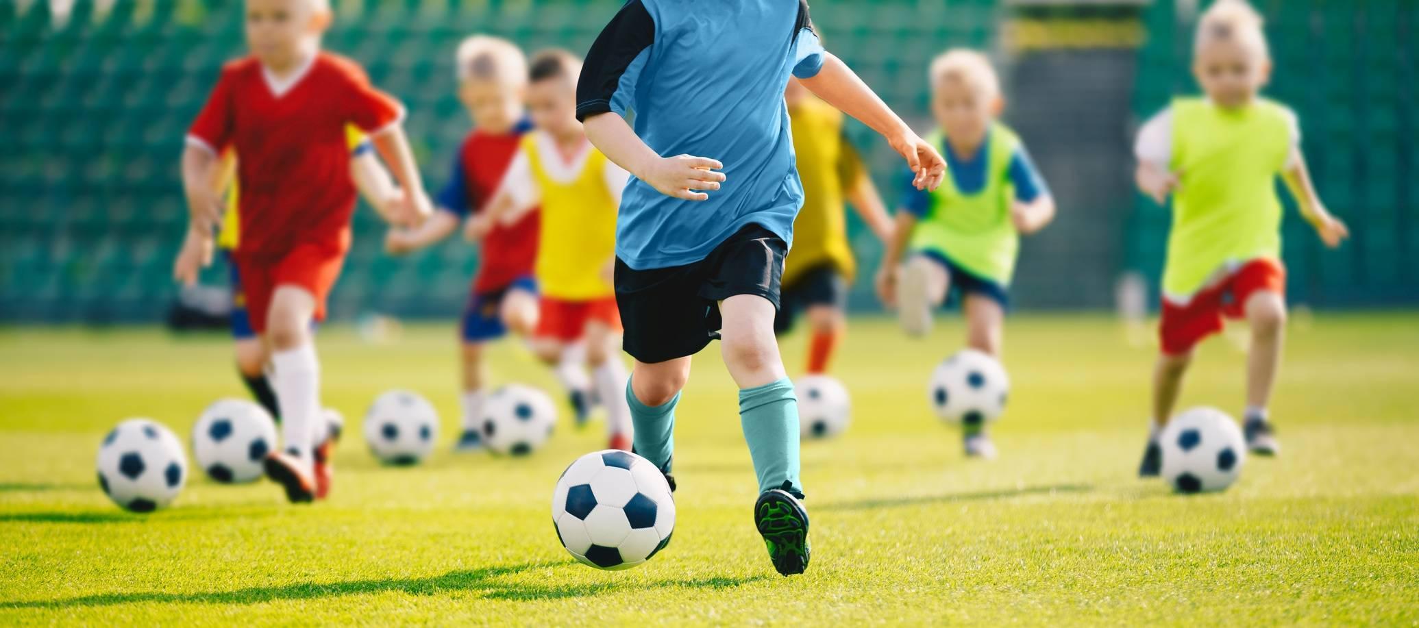 Mali chłopcy grają w piłkę nożną. Jak powinna wyglądać dieta dla aktywnego dziecka i jak skomponować jadłospis dla trenujących dzieci?