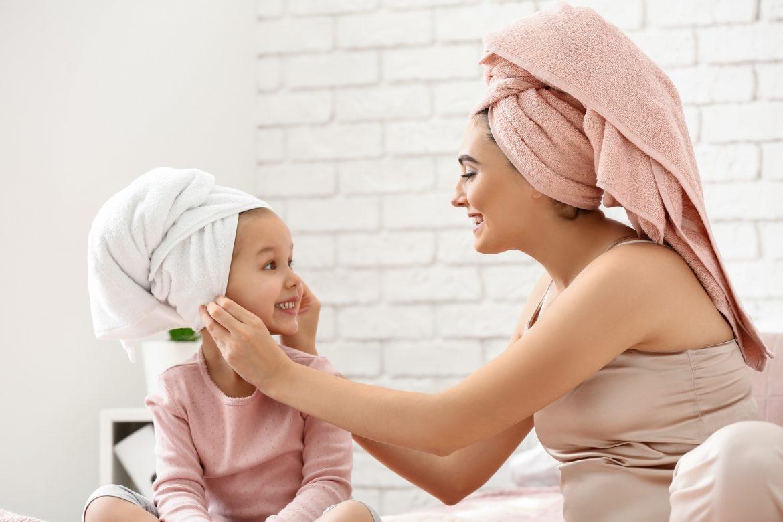 Atopowe zapalenie skóry - kąpiele lecznicze. Mama i córka po kąpieli w piżamach i ręcznikach zawiniętych na głowie.