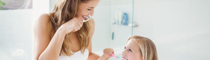 Jak dbać o zdrowe i mocne zęby i higienę jamy ustnej? Mama i córeczka ubrane w białe koszulki myją zęby w łazience.