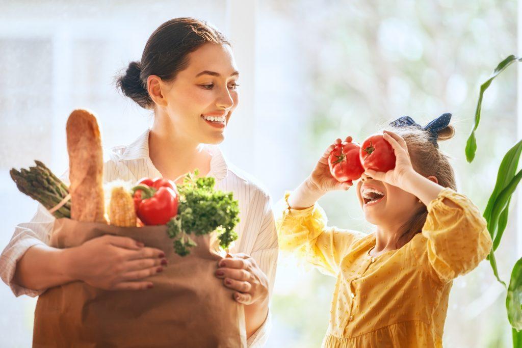 Witaminy na odporność - czy warto je suplementować? Mama i córka niosą zakupy w papierowej torbie.