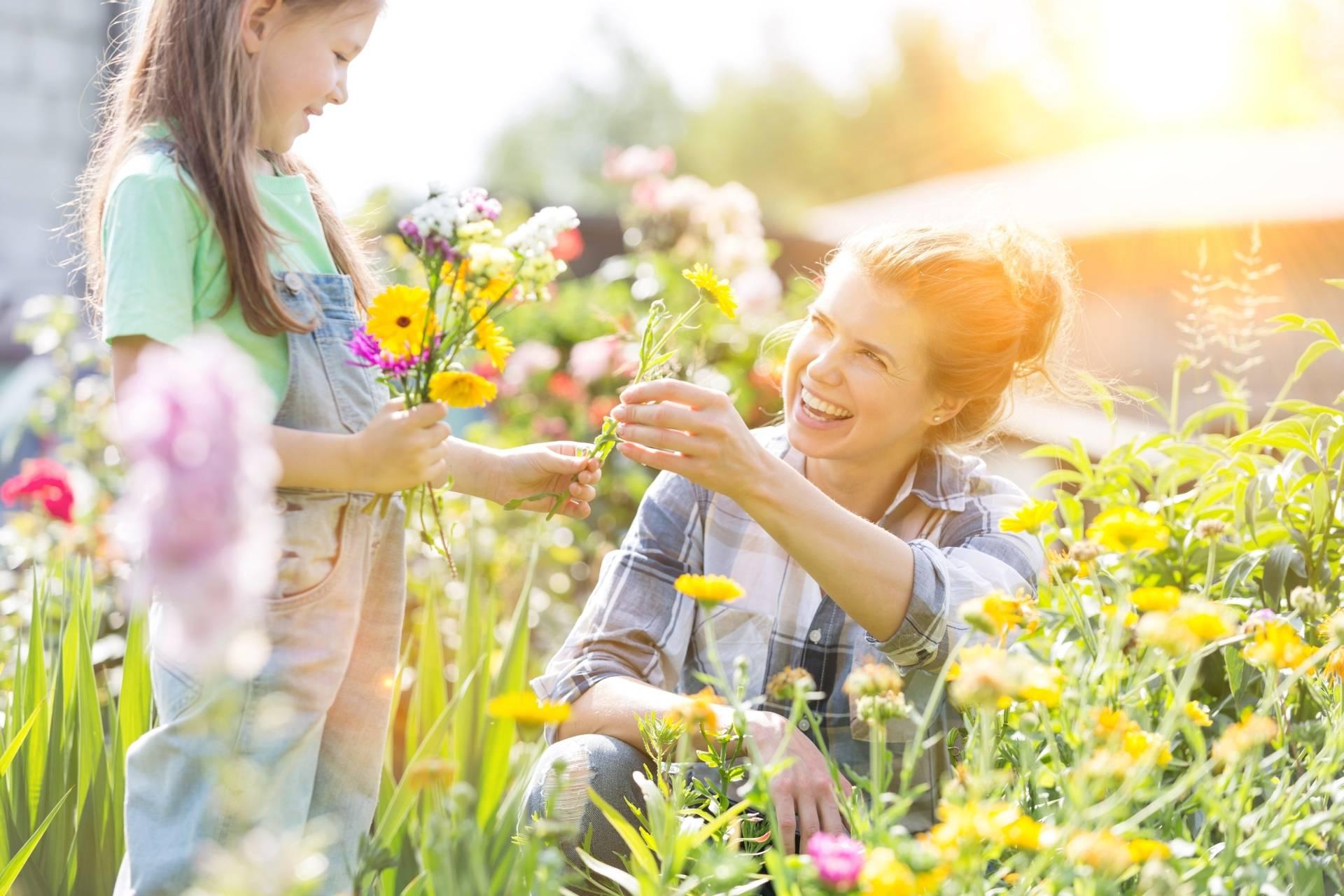 Work-life balance. Młoda kobieta pracuje w ogródku, zrywa kwiatka i podaje go swojej córce. Letnia sceneria.