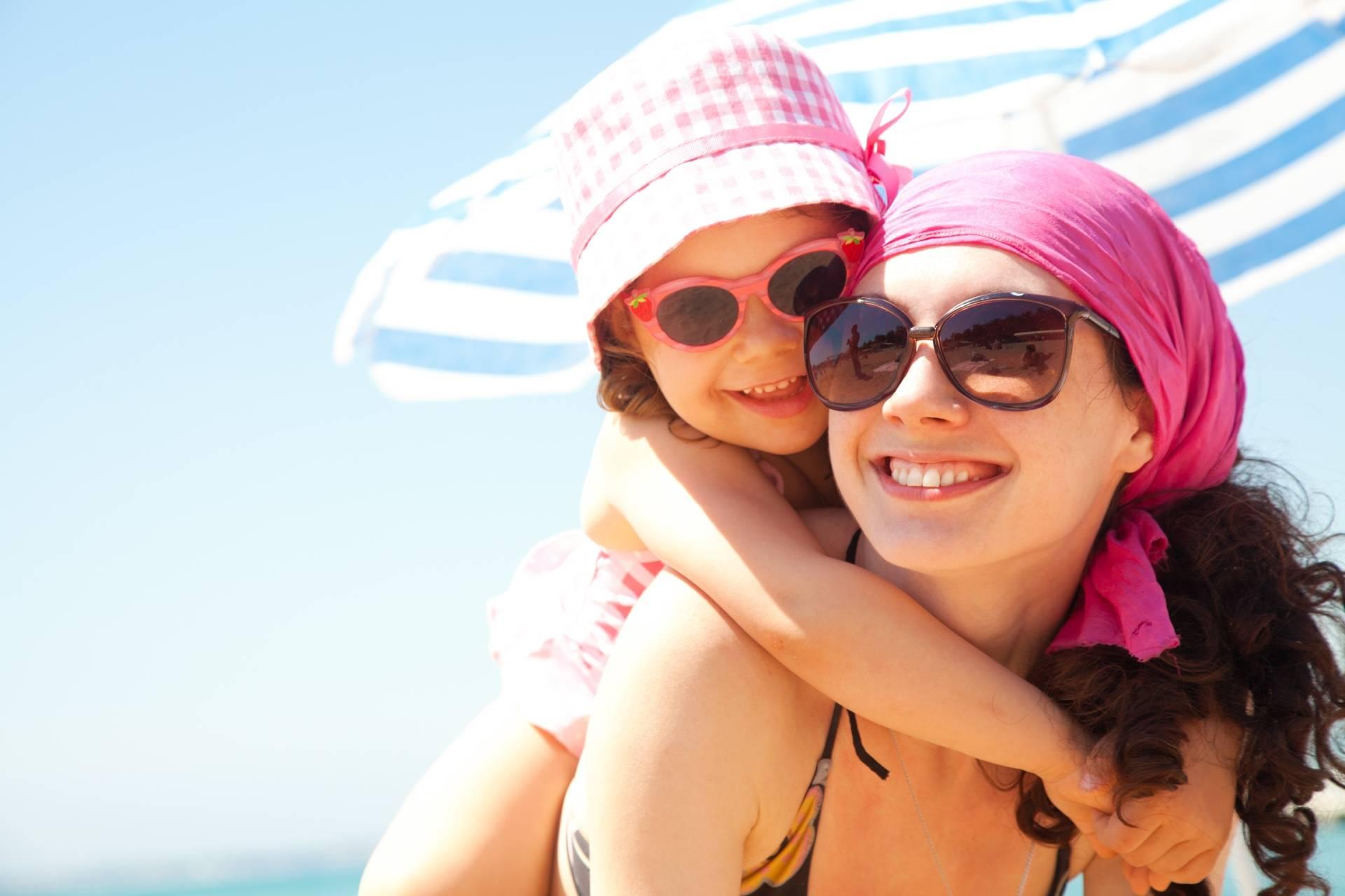 Dziewczynka przytula się do mamy na plaży. Udar słoneczny u dzieci - jak chronić i jak zareagować?