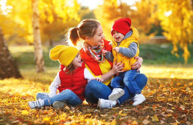 Jak zadbać o siebie jesienią wg medycyny chińskiej? Mama z dziećmi bawi się w jesiennych liściach.