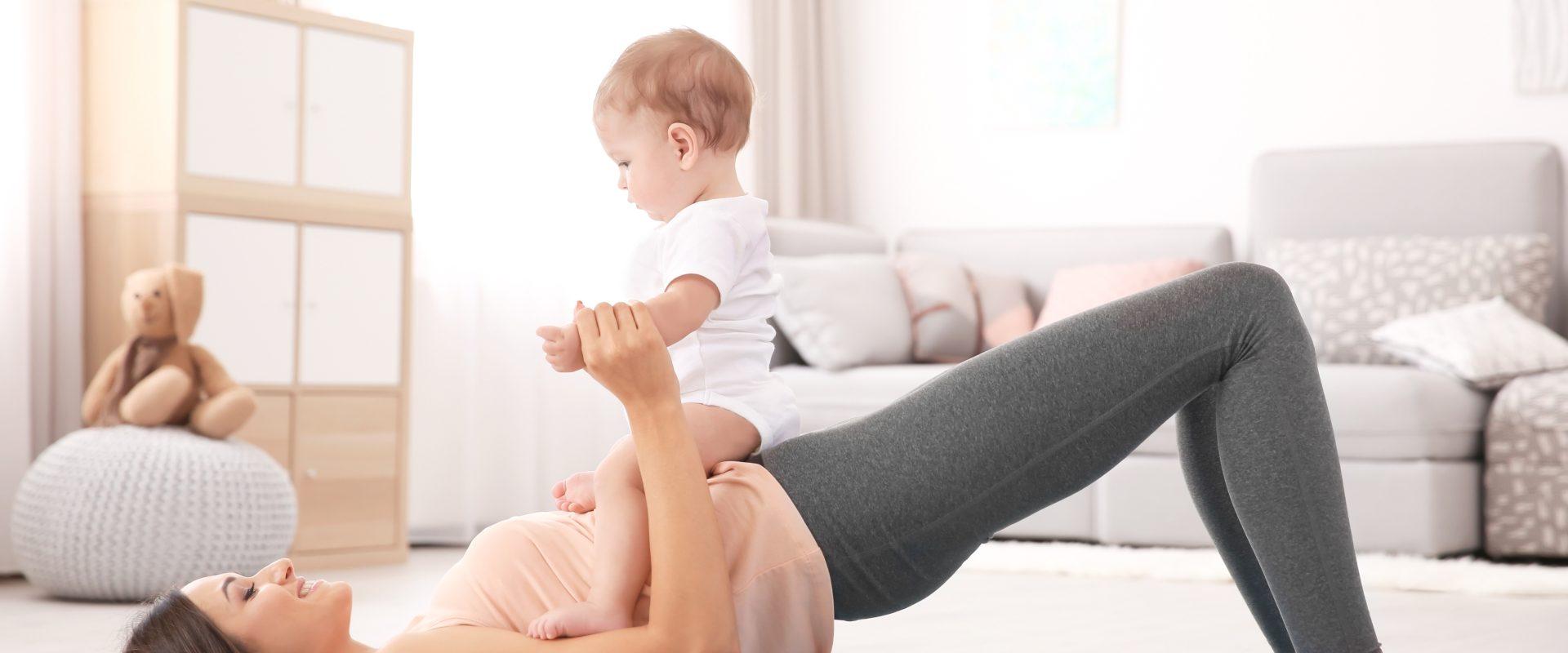 Ćwiczenia po porodzie - jak je wykonać i jakie będą bezpieczne? Mama ćwiczy z niemowlakiem na biodrach na macie w domu.
