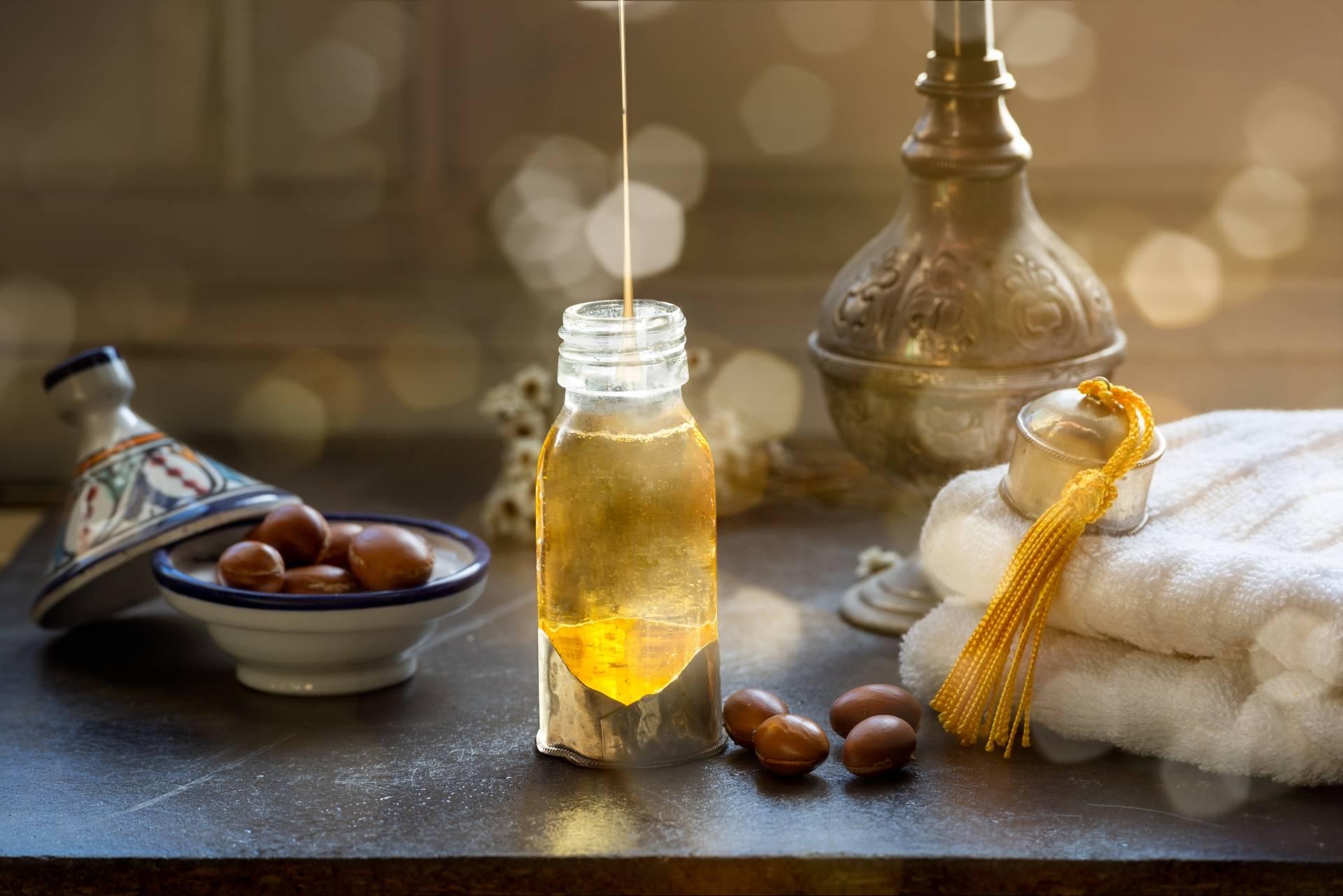Olejek arganowy z Maroka w starożytnej stylizacji. Buteleczka oleju, orzechy drzewa arganii w miseczce ręcznik.