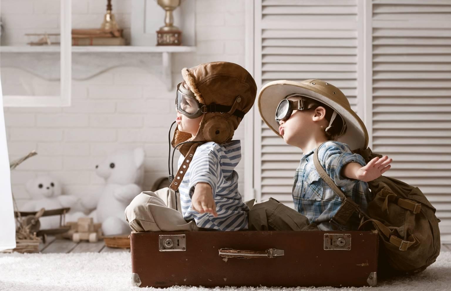 Wakacje z dziećmi - co powinna zawierać apteczka turystyczna? Dzieci bawią się w podróżników lotników siedząc w starej walizce.