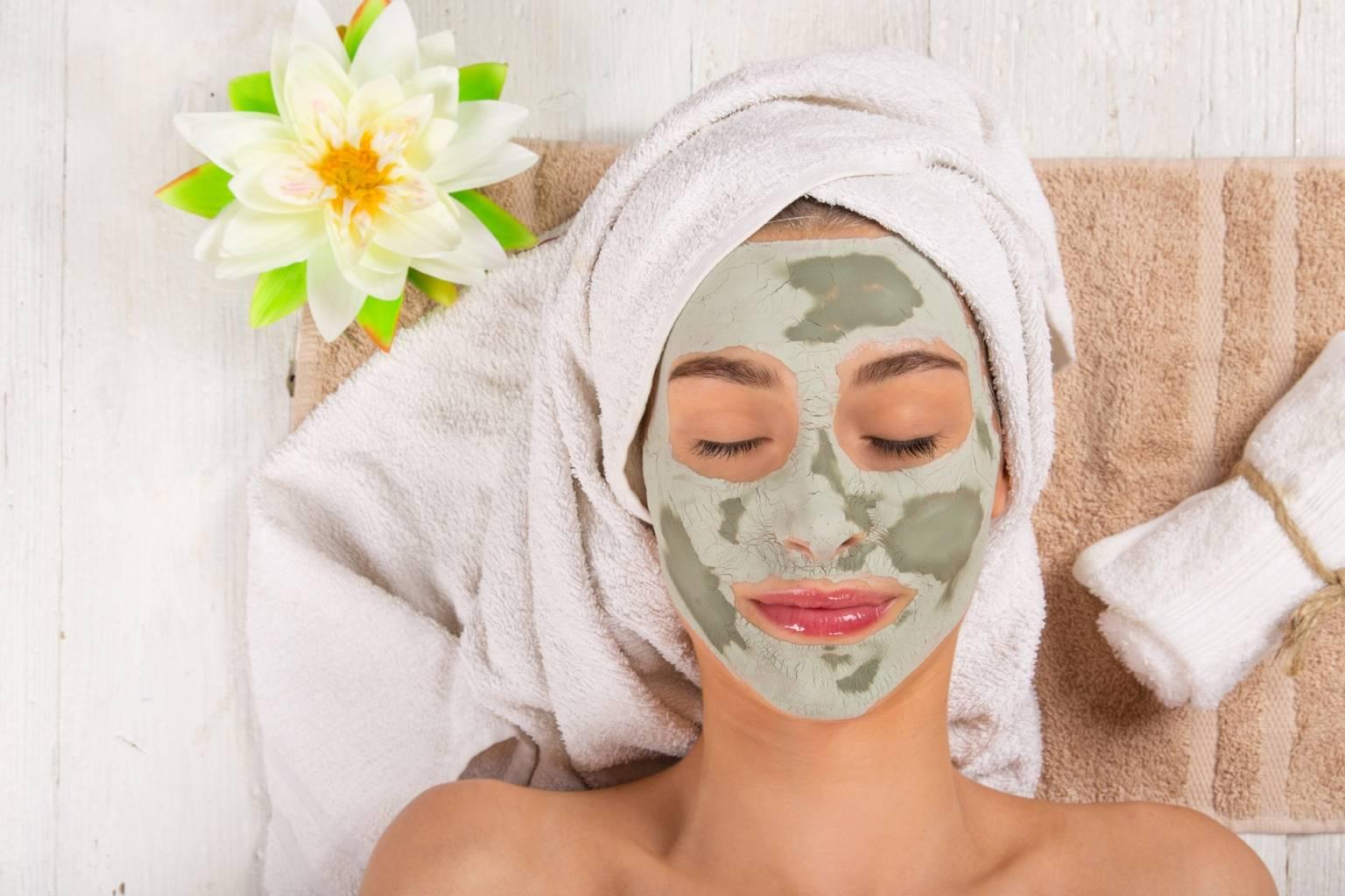 Zabiegi kosmetyczne z glinką bentonitową - kobieta relaksuje się z maseczką na twarzy i ręcznikiem na głowie.