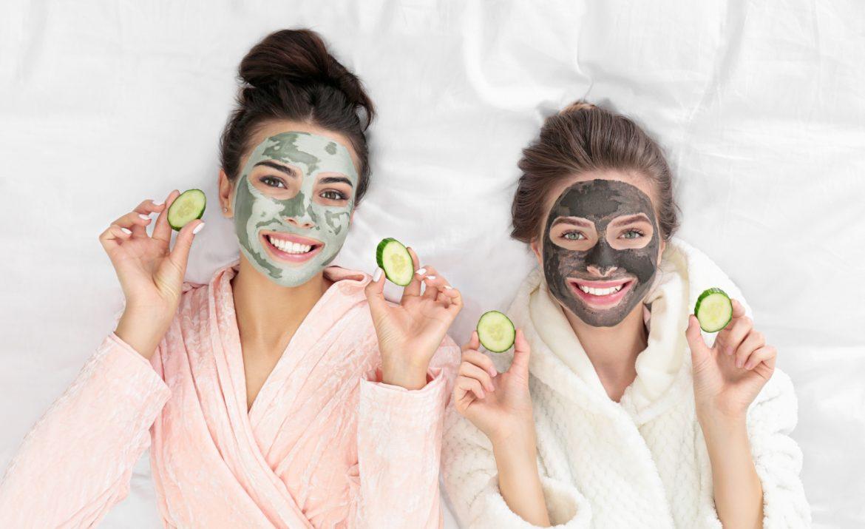 Maseczki na twarz - jakie są najlepsze i jak je stosować? Jak zrobić domowe maseczki DIY i jakie maseczki z drogerii będą odpowiednie? Dwie przyjaciółki w szlafrokach, z maseczkami na twarzy leżą na łóżku i trzymają plasterki ogórka w dłoni.