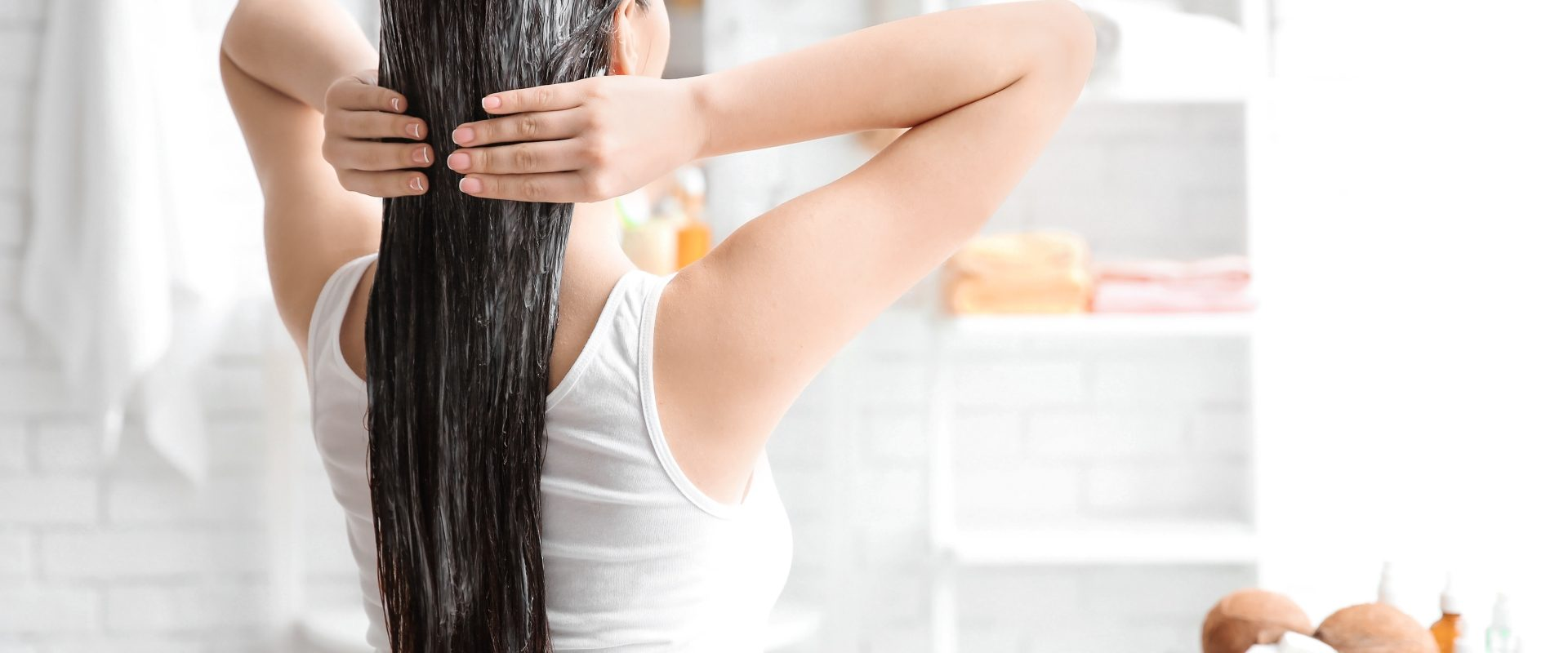 Naturalne kosmetyki do włosów DIY. Maseczki do włosów ekologiczne. Młoda kobieta stoi tyłem w swojej łazience i wciera we włosy domową maseczkę. W tle widać kokosy.