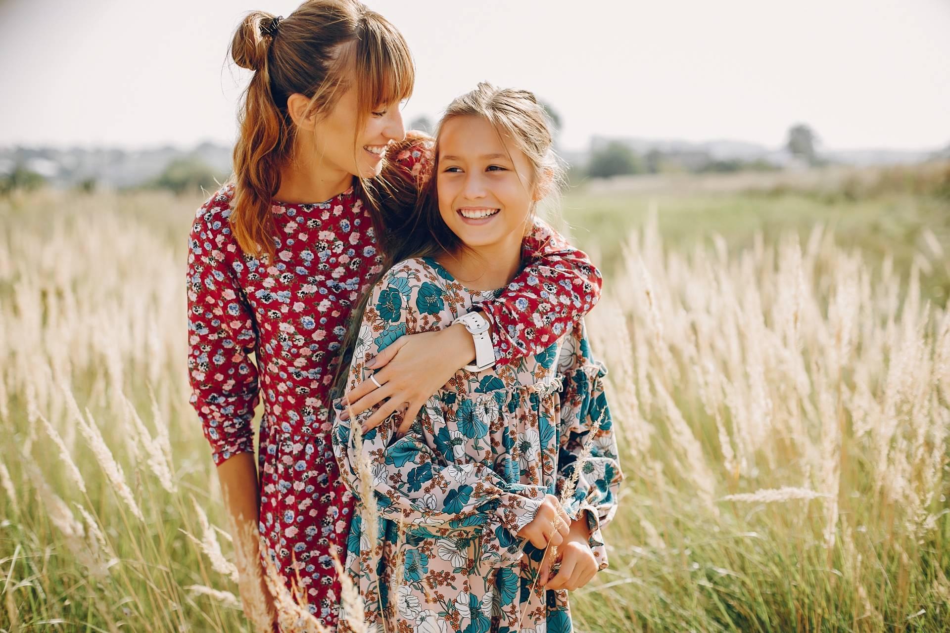 Alergia na pyłki - co musisz o niej wiedzieć? Przytulone mama i córka ubrane w kwieciste sukienki stoją w polu zbóż.