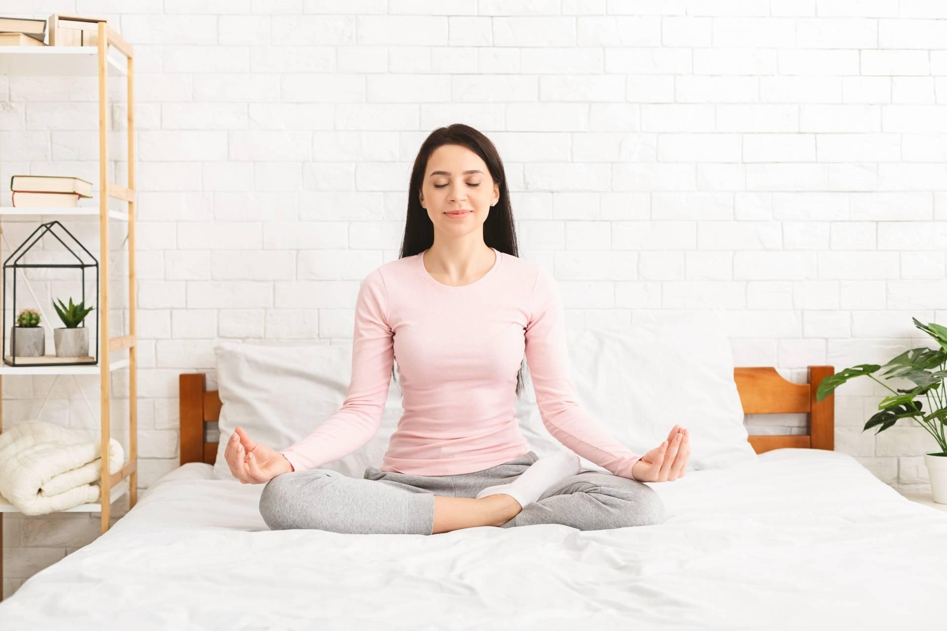 Jak medytować? Medytacja dla początkujących. Młoda kobieta siedzi na łóżku i sypialni w pozycji kwiatu lotosu i medytuje.