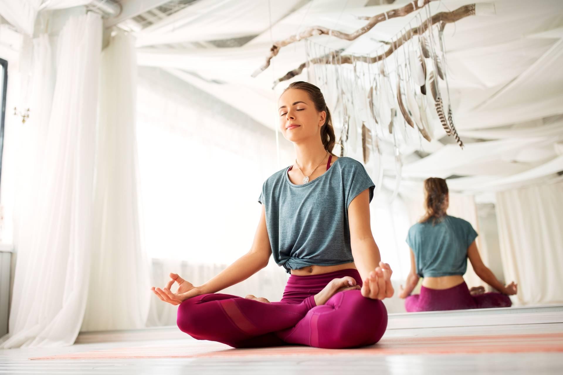 Medytacja - jak medytować? Młoda kobieta w szarym t-shircie i bordowych legginsach siedzi po turecku na sali gimnastycznej i medytuje.