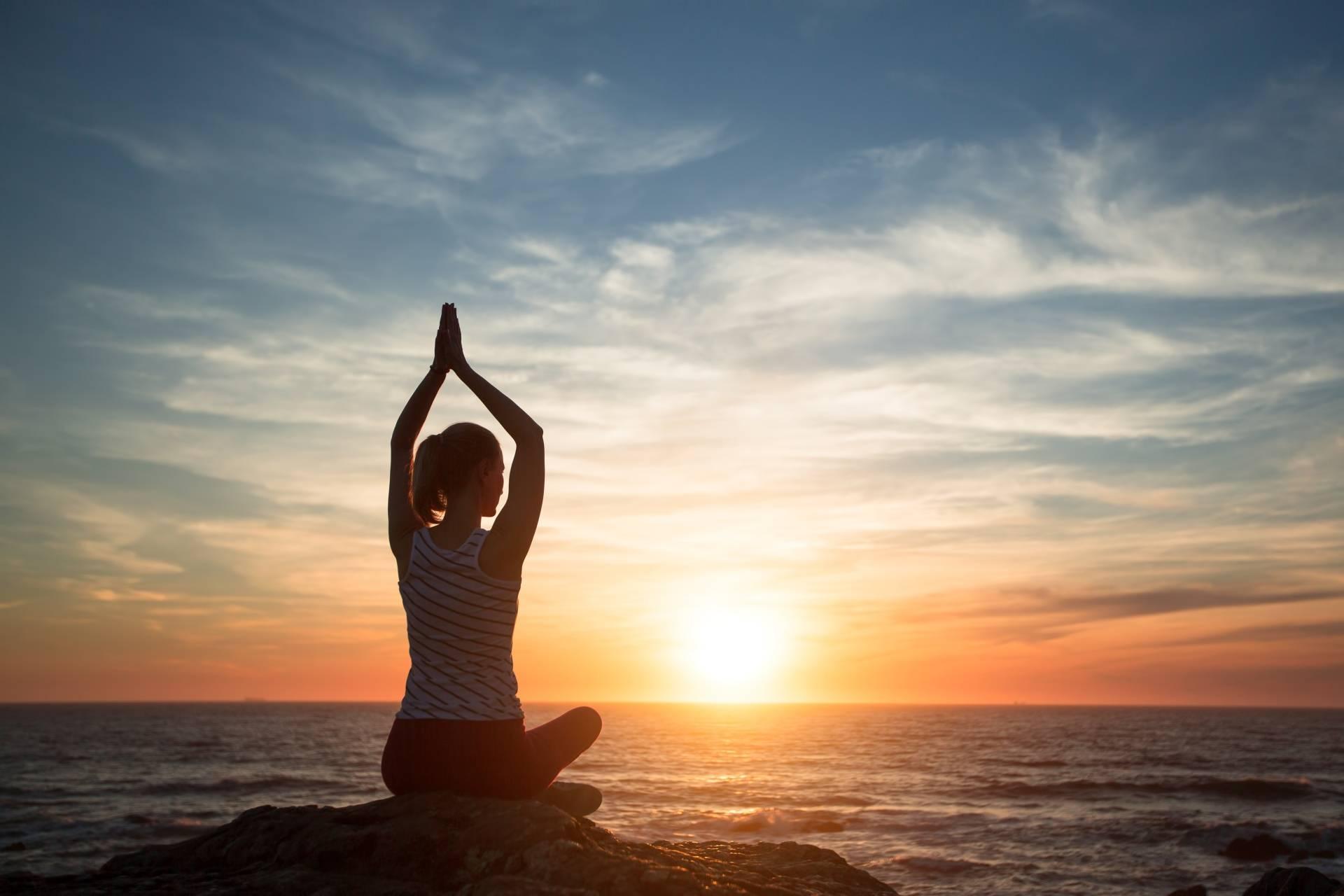 Jak medytować? Medytacja dla początkujących. Kobieta siedzi na skarpie nad oceanem o zachodzi słońca i medytuje.