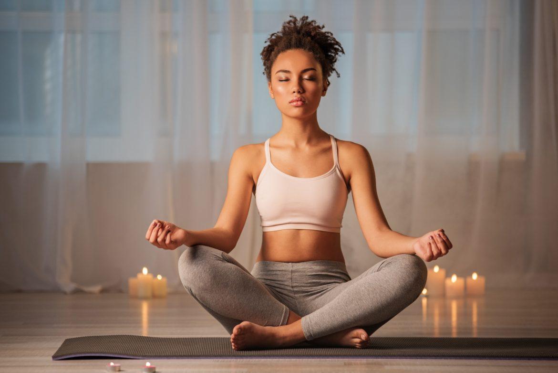 Joga i ajurweda na stres i dobry sen. Młoda kobieta medytuje wieczorem w domu przy świecach.