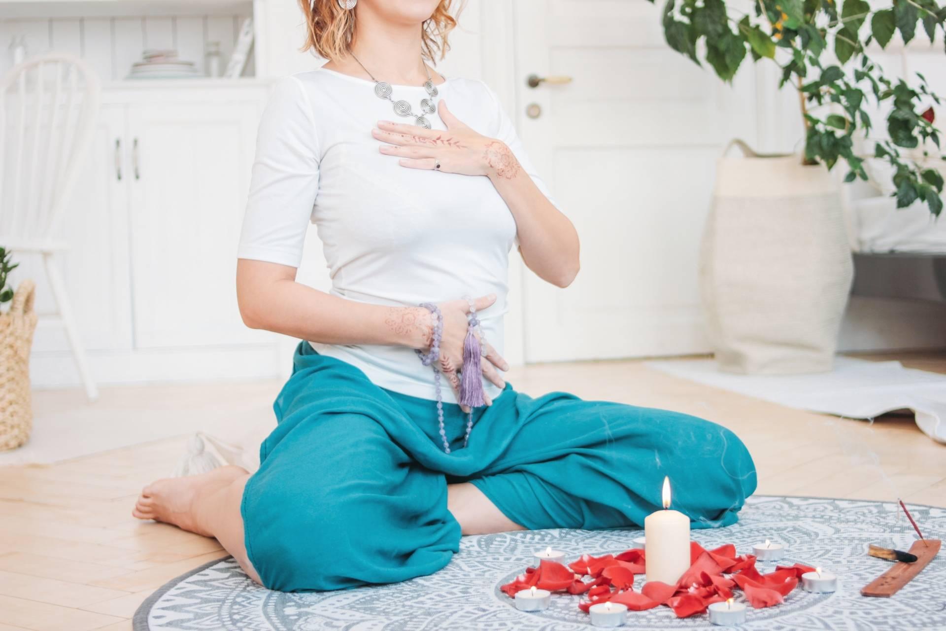 Kobieta medytuje przy zapalonej świecy. Medytacja, joga i ajurweda - sposoby na stres i dobry sen.