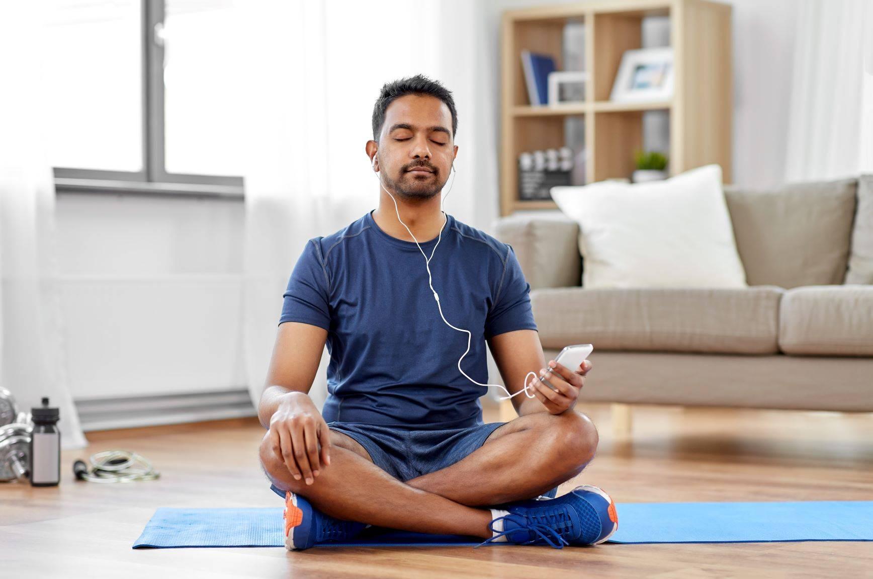 Aplikacja do medytacji - jak działa i jakie daje korzyści? Mężczyzna medytuje z aplikacją do medytacji na macie w domu.