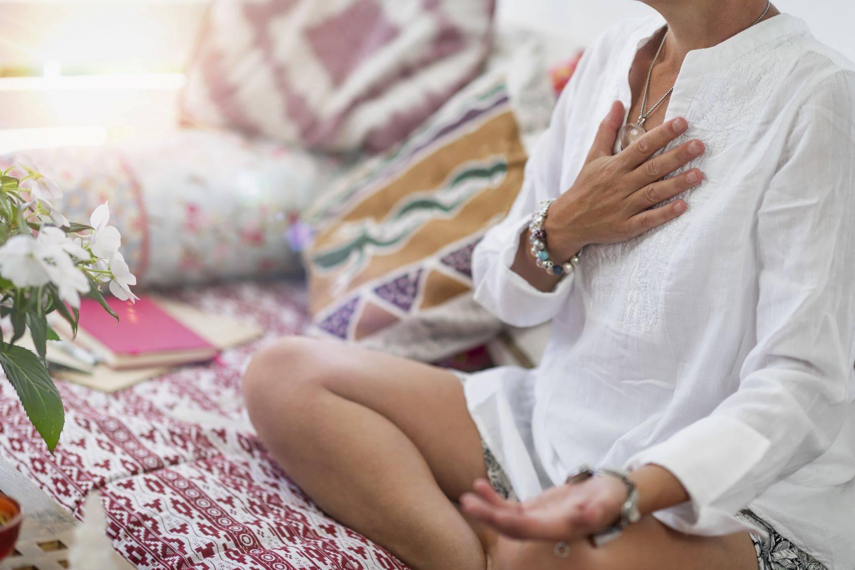 Medytacja dla początkujących. Aplikacja do medytacji. Kobieta w białej koszuli medytuje na kanapie.