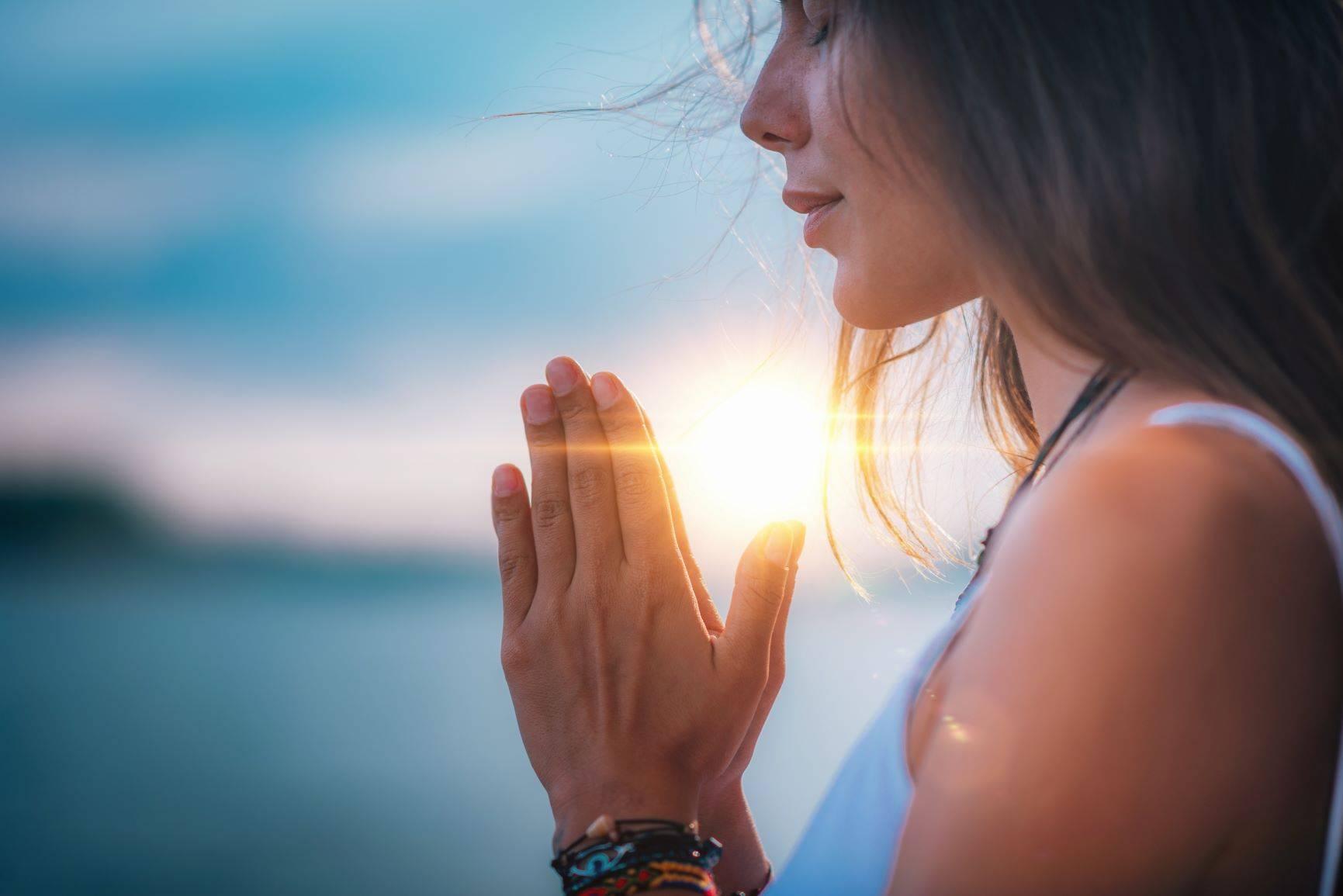 Jakie są korzyści duchowe z medytacji? Kobieta medytuje nad wodą.