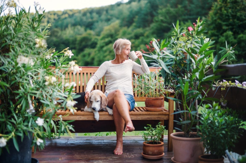 Menopauza - jak łagodzić objawy klimakterium? Kobieta w okresie przekwitania siedzi na ławce w ogrodzie i pije kawę i głaszcze psa.