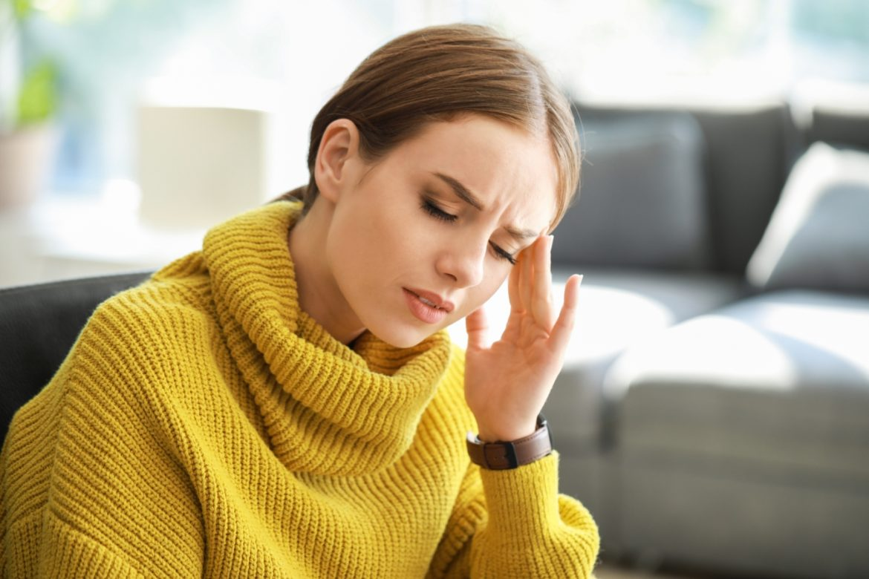 Migrena - objawy, przyczyny i leczenie. Migrena z aurą i migrena oczna. Kobieta cierpiąca na migrenę dotyka dłonią bolącej skroni.