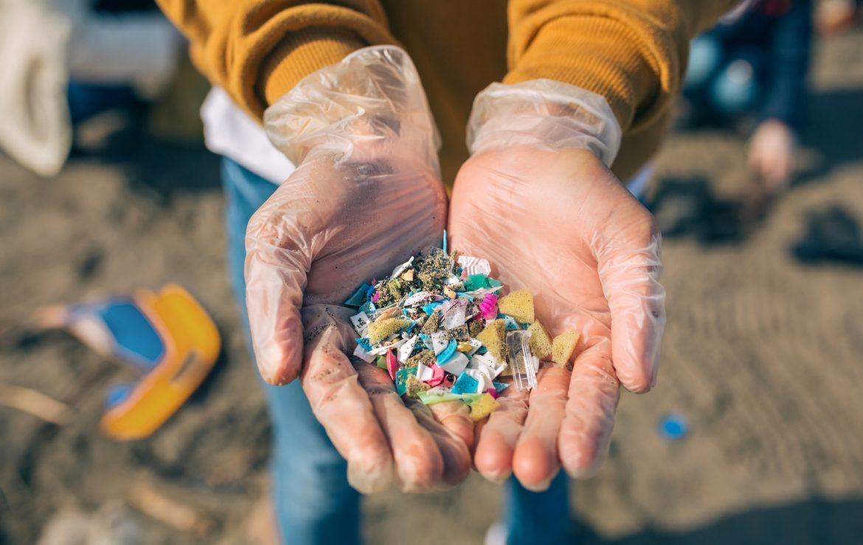 Mikroplastik - jak bardzo jest szkodliwy? Kobieta pokazuje na dłoniach małe cząsteczki plastiku zebrane na plaży.