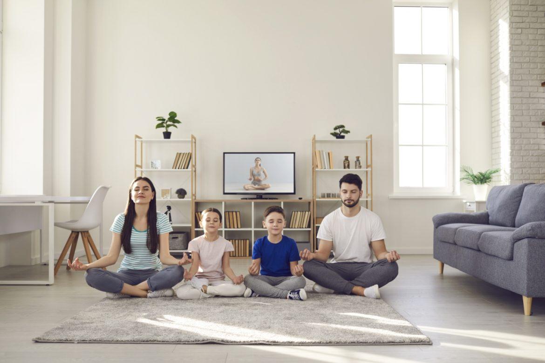 Mindfulness dla dzieci. Rodzina - mama, tata i dwójka dzieci - trenują uważność i medytują w salonie w domu.