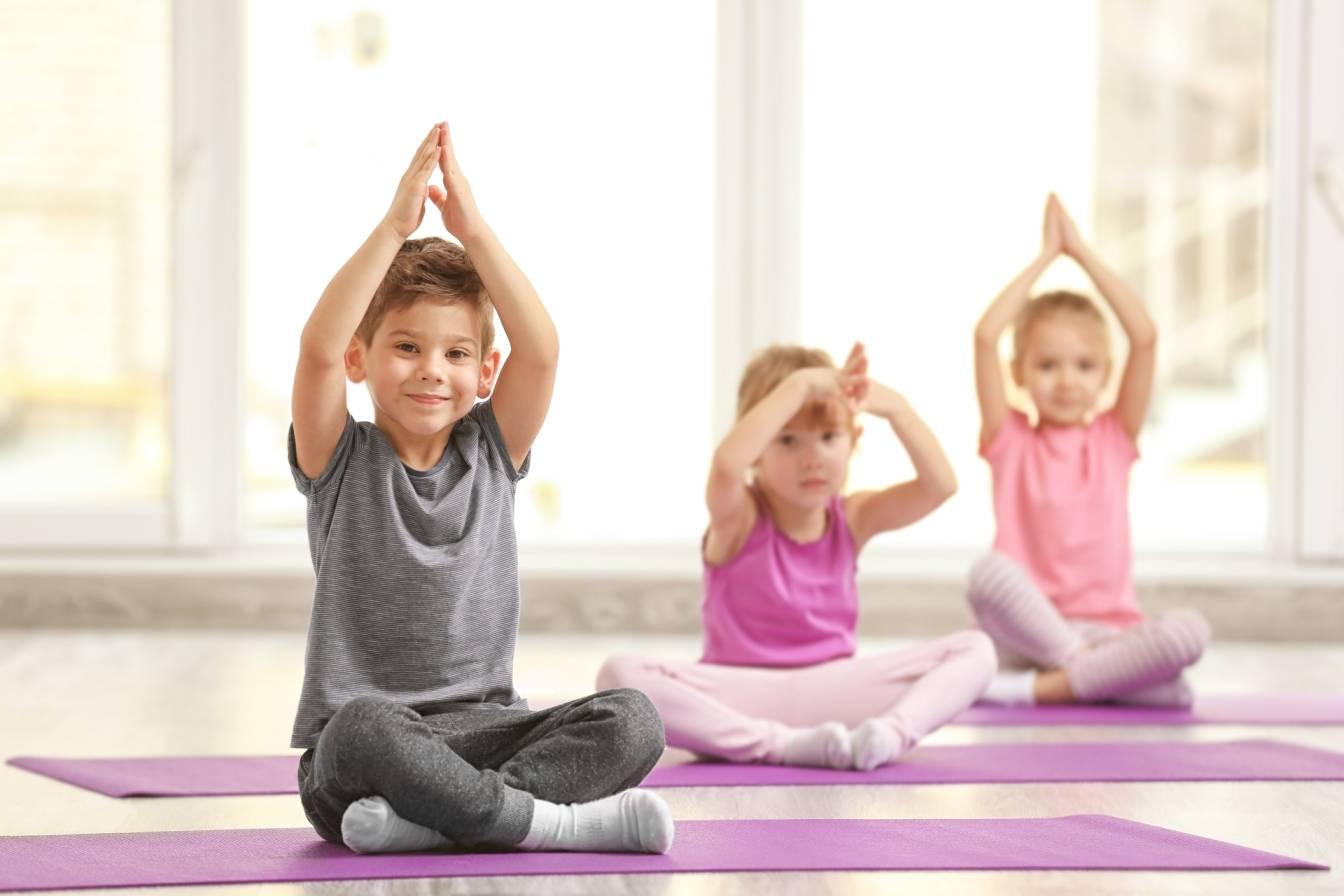 Mindfulness dla dzieci - na czym polegają treningi uważności dla maluchów i nastolatków? Przedszkolaki siedzą na matach w sali gimnastycznej i trenują jogę i medytację.