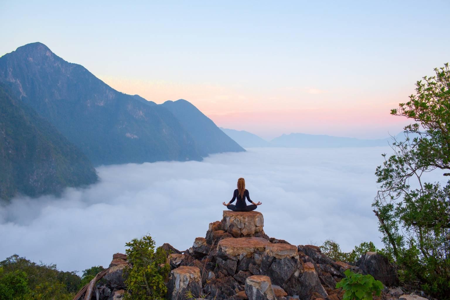 Mindfulness - trening uważności. Kobieta medytuje na skale w górach.