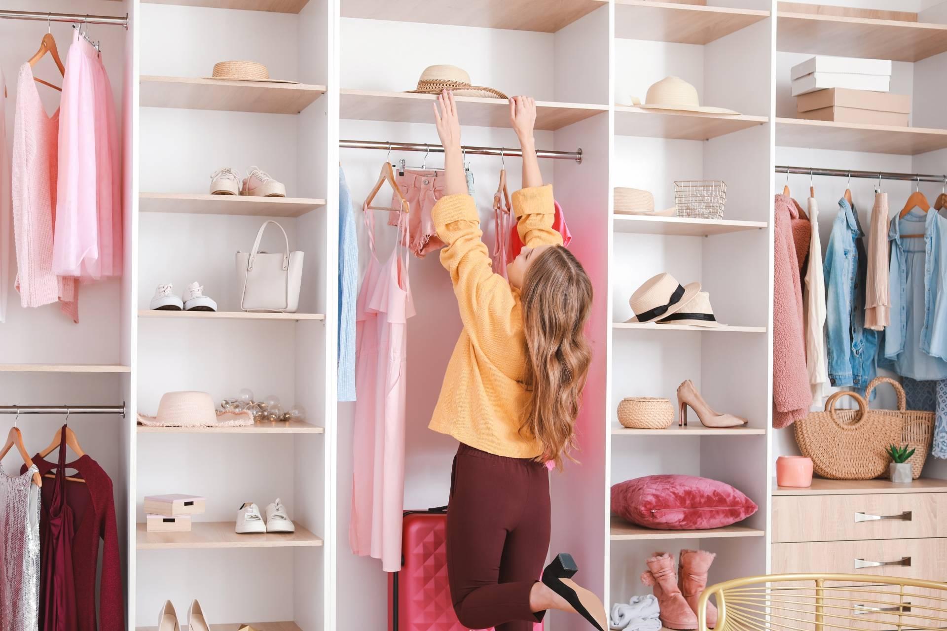 Porządki w szafie - na czym polega minimalizm? Kobieta układa ubrania w swojej garderobie.