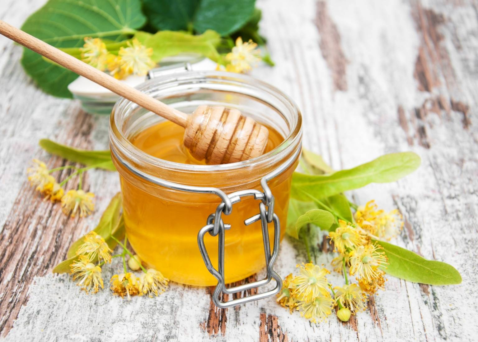 Lipa z miodem. Miód w słoiku na rustykalnym blacie, obok leży gałązka z kwiatami lipy.