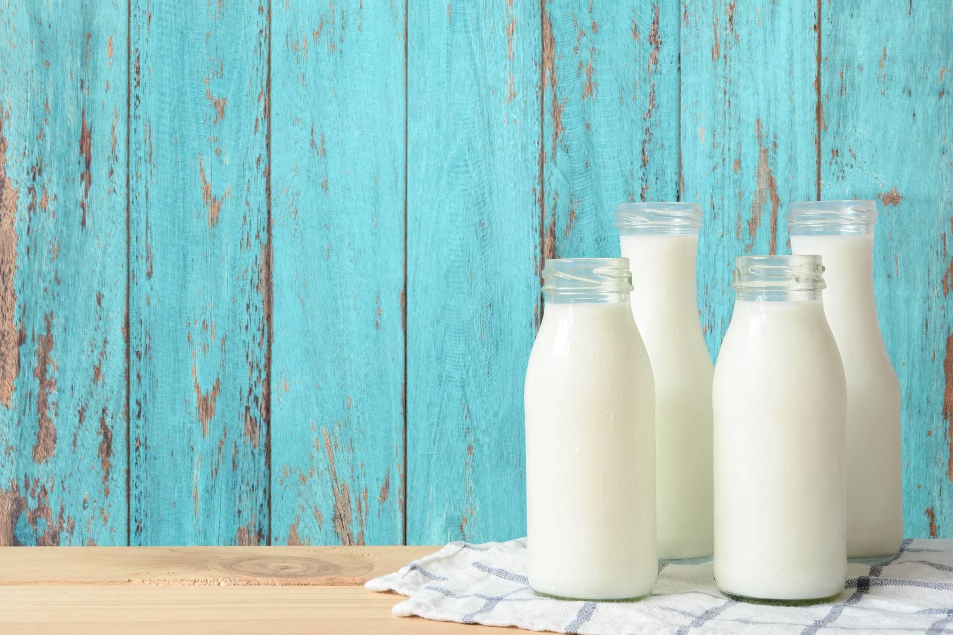 Mleko bez laktozy - kto powinien je pić? 4 butelki mleka stoją na stole na tle pomalowanego na niebiesko płotu.