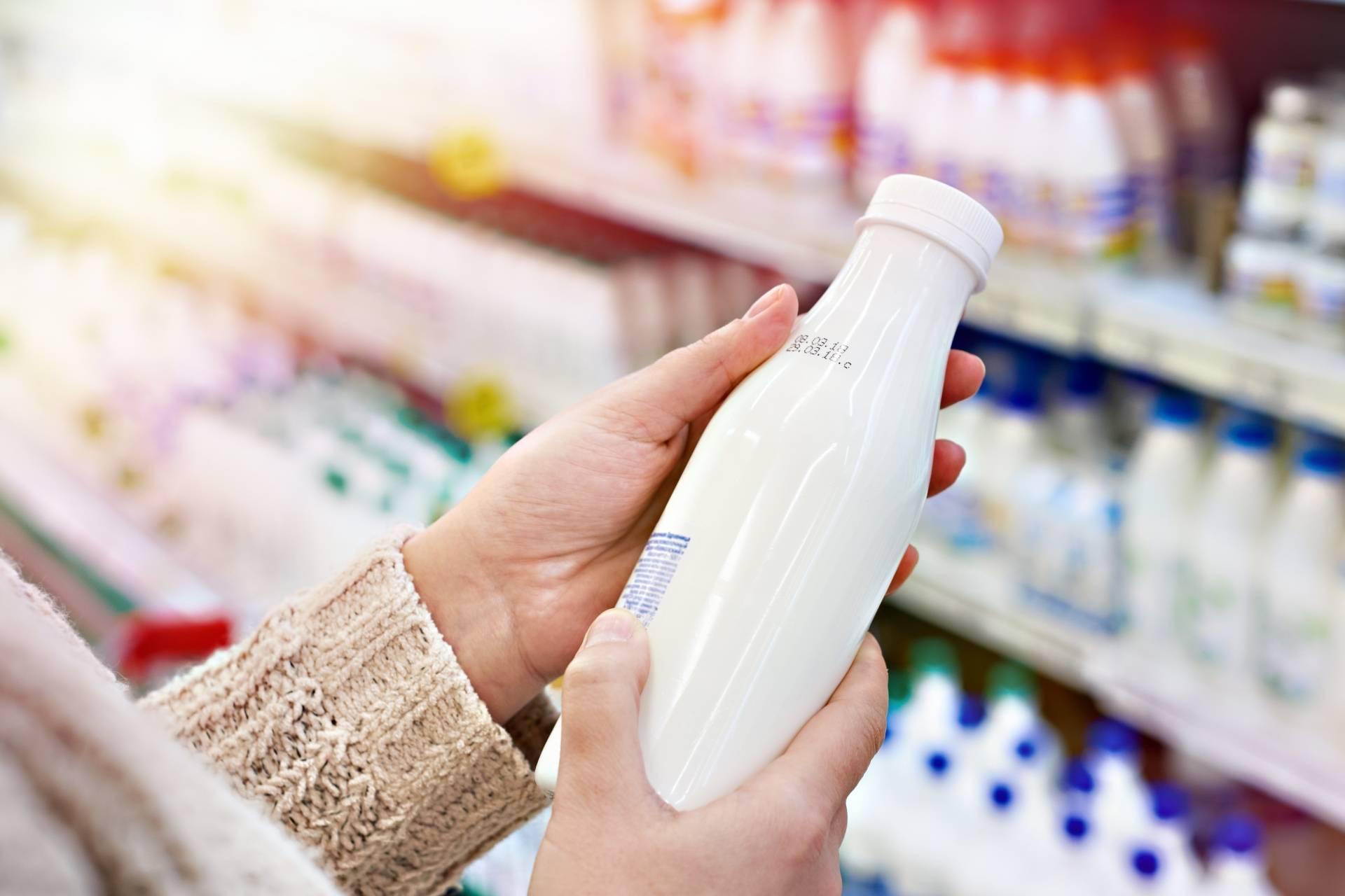 Mleko bez laktozy - co musisz o nim wiedzieć? Kobieta wybiera w sklepie mleko - w tle półki sklepowe z nabiałem.