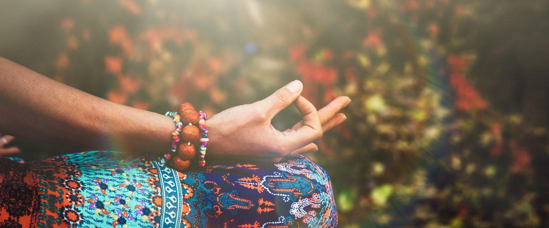 Mudry - gesty dłoni w ajurwedzie. Kobieta ćwiczy jogę lub medytuje układając dłonie w mudry.