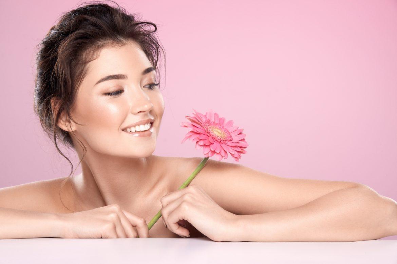 Jak zadbać o cerę naczynkową? Młoda kobieta o pięknej rumianej cerze na różowym tle opiera się o blat i trzyma w ręku różowy kwiatek.