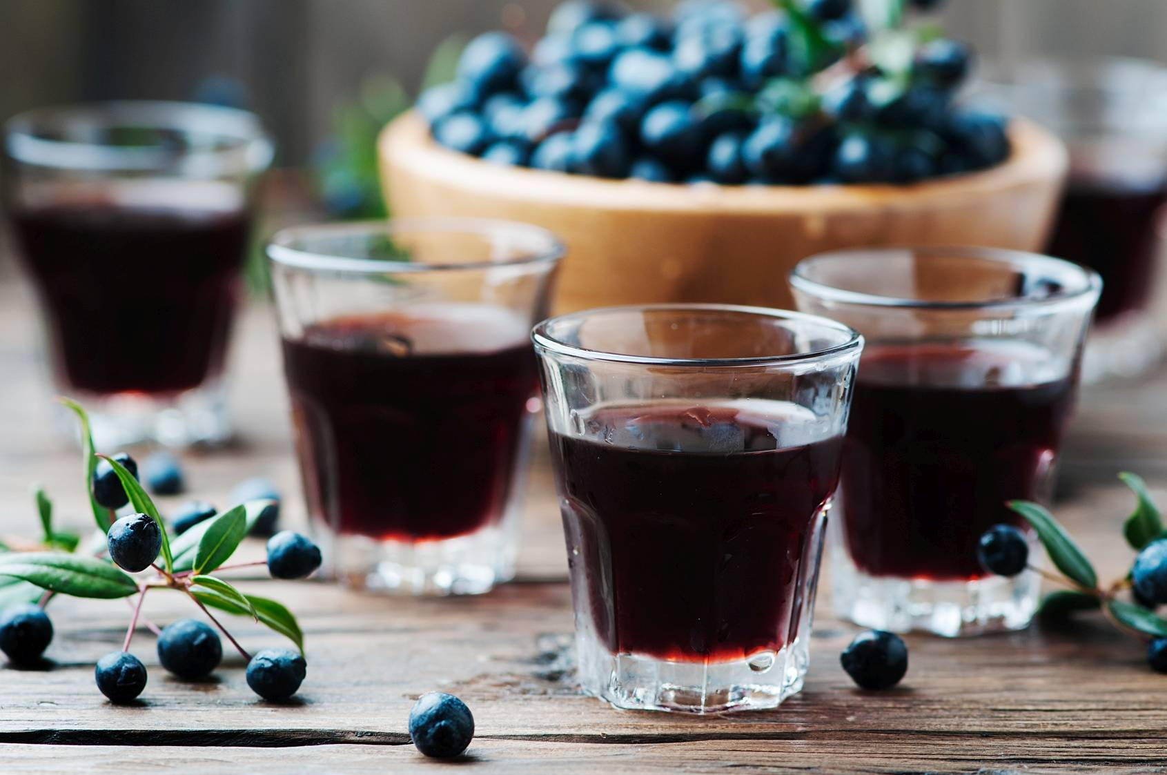 Nalewki lecznicze. Na drewnianym stole stoją kieliszki z nalewką z ciemnych owoców, w tle stoi drewniana miska z granatowymi owocami.