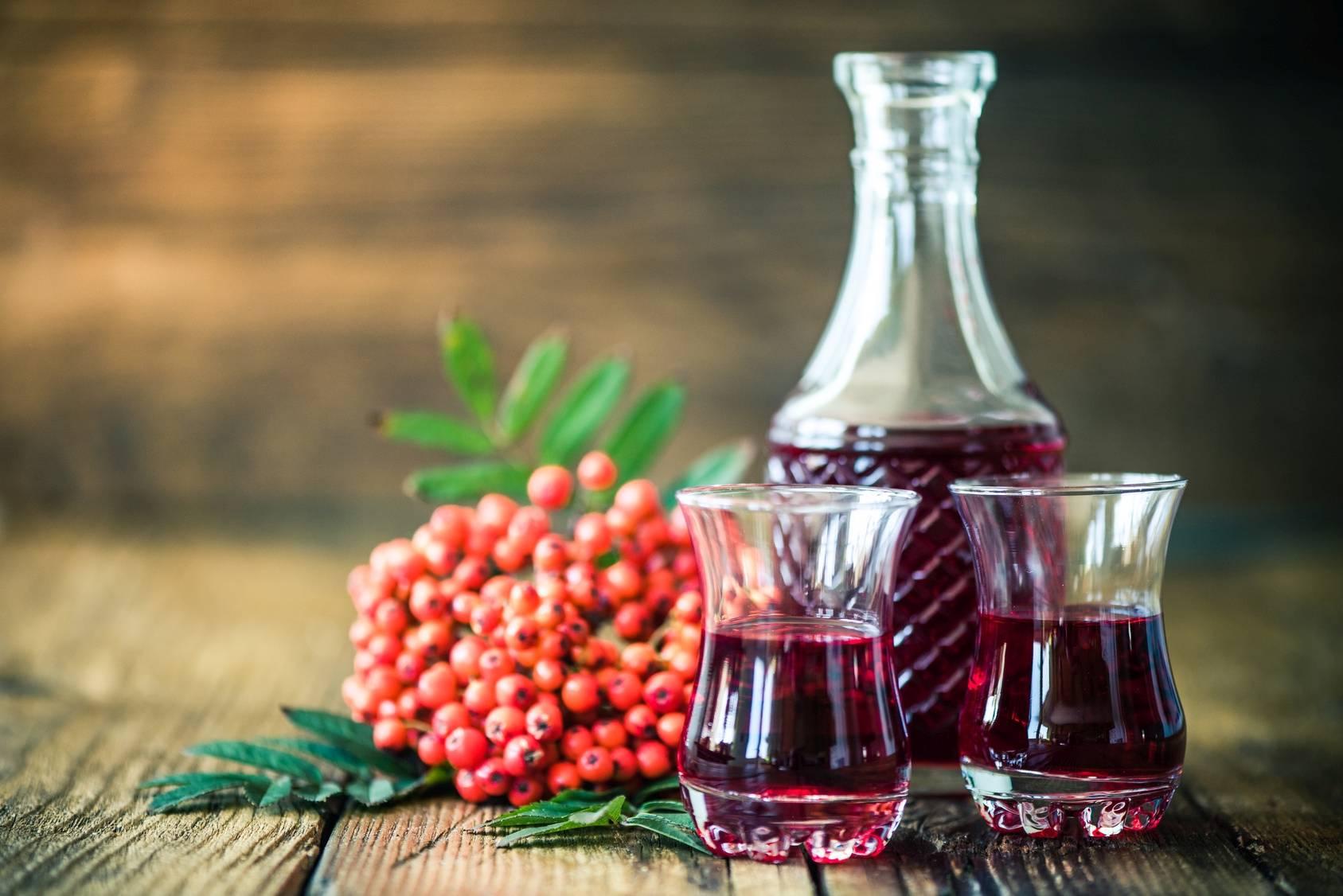Przepisy na nalewki z jarzębiny, kasztanów i tarniny. Sprawdź, jakie mają właściwości lecznicze. Nalewka z jarzębiny w karafce i szklankach na drewnianym blacie.