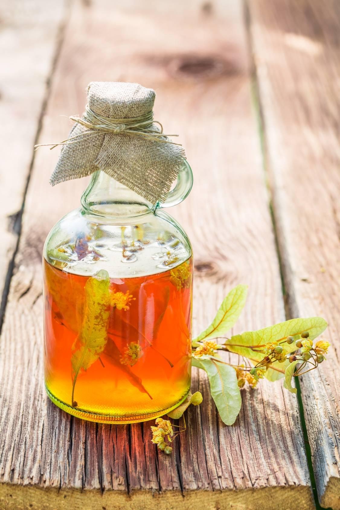 Butelka nalewki leczniczej z lipy o pomarańczowym zabarwieniu stoi na drewnianym stole. Obok leży ususzona gałązka z liśćmi lipy.