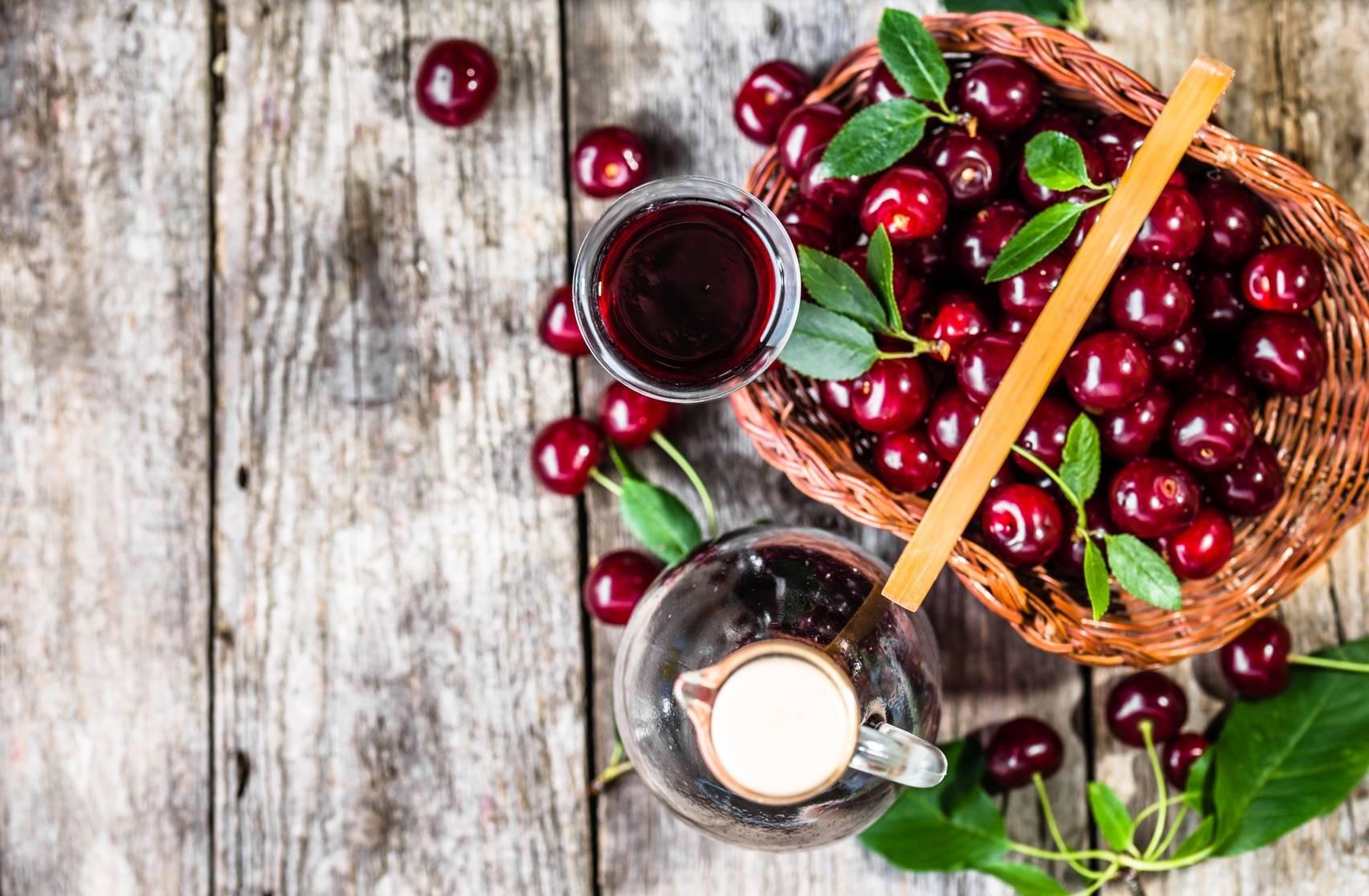 Lecznicze nalewki: wiśniówka. Na rustykalnym stole stoi butelka wiśniówki, obok stoi kieliszek z nalewką i kosz wiklinowy pełen wiśni.