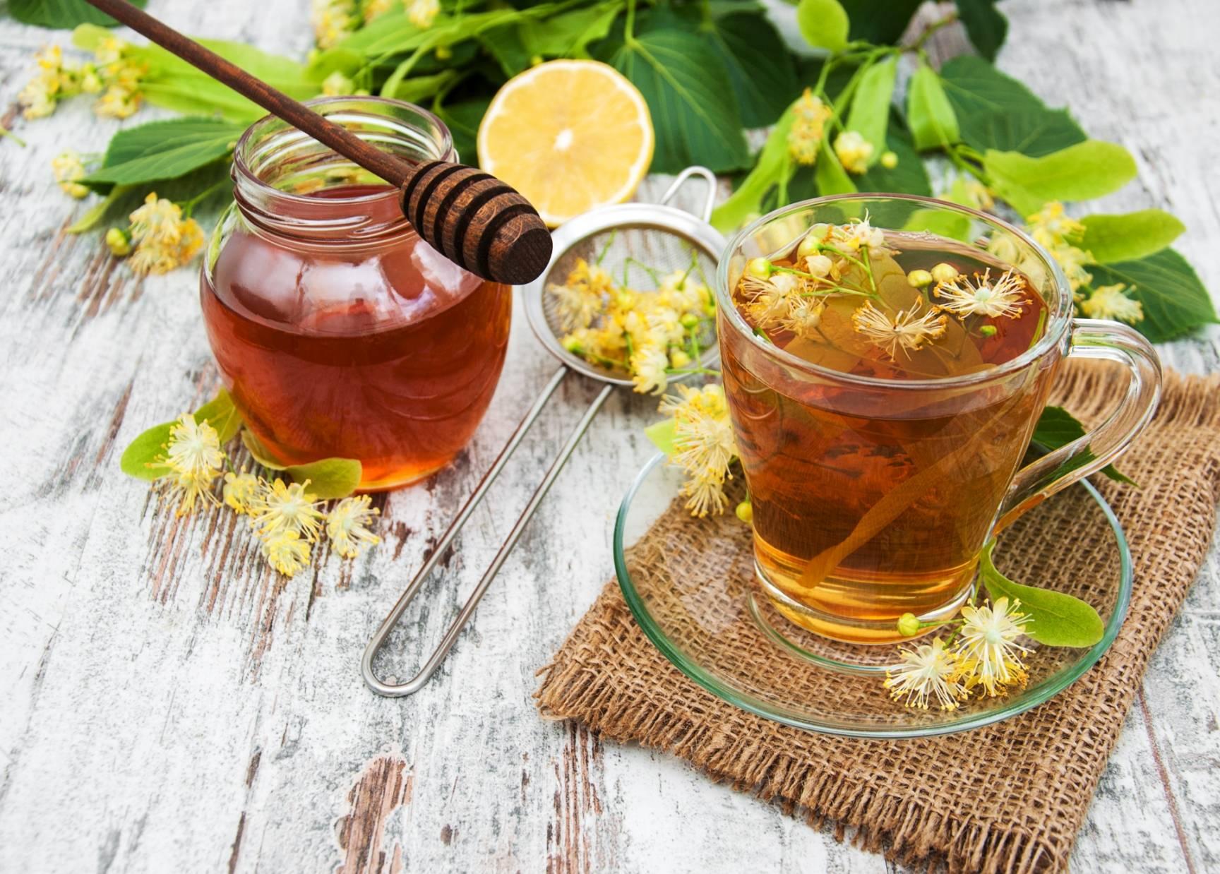 Herbata z lipy w szklance na spodku, obok stoi słoik miodu i leżą kwiaty lipy. Lipa na stres i przeziębienie.