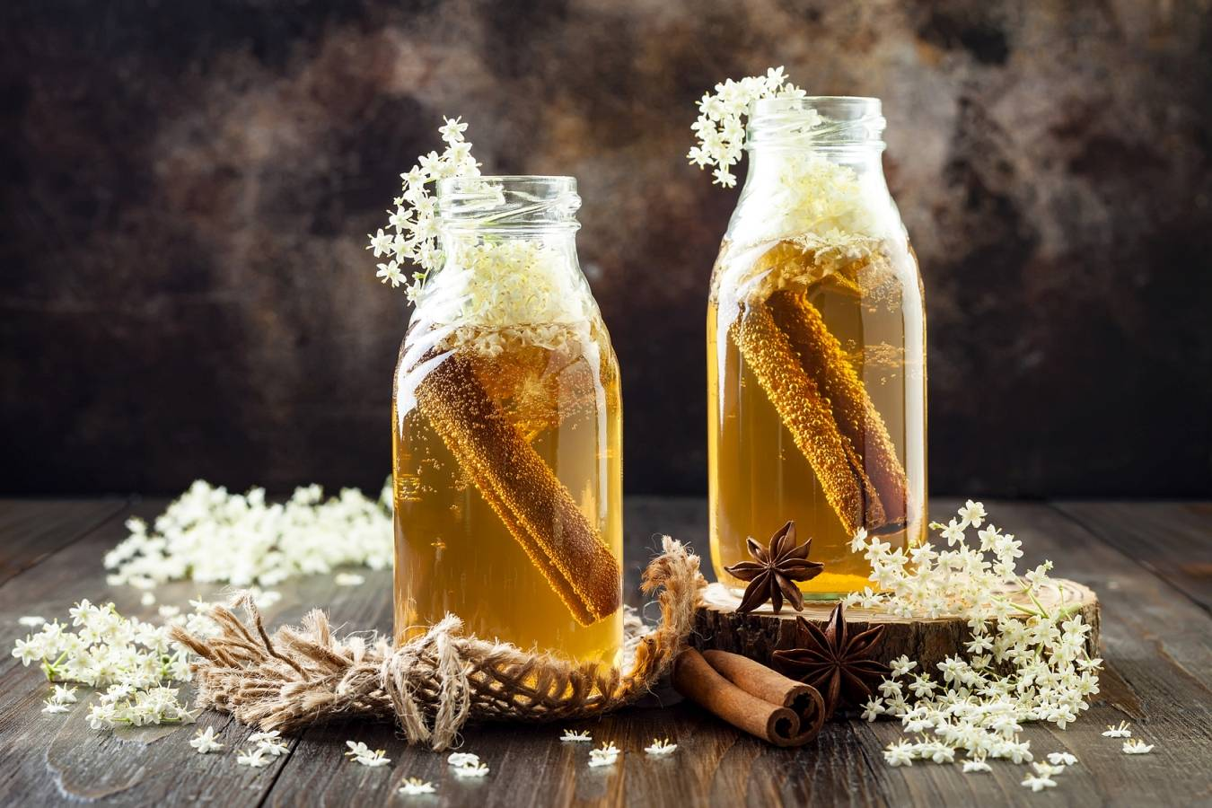 Jak leczyć przeziębienie według medycyny chińskiej? Syrop z kwiatów czarnego bzu i cynamonu w szklanych butelkach na drewnianym blacie.