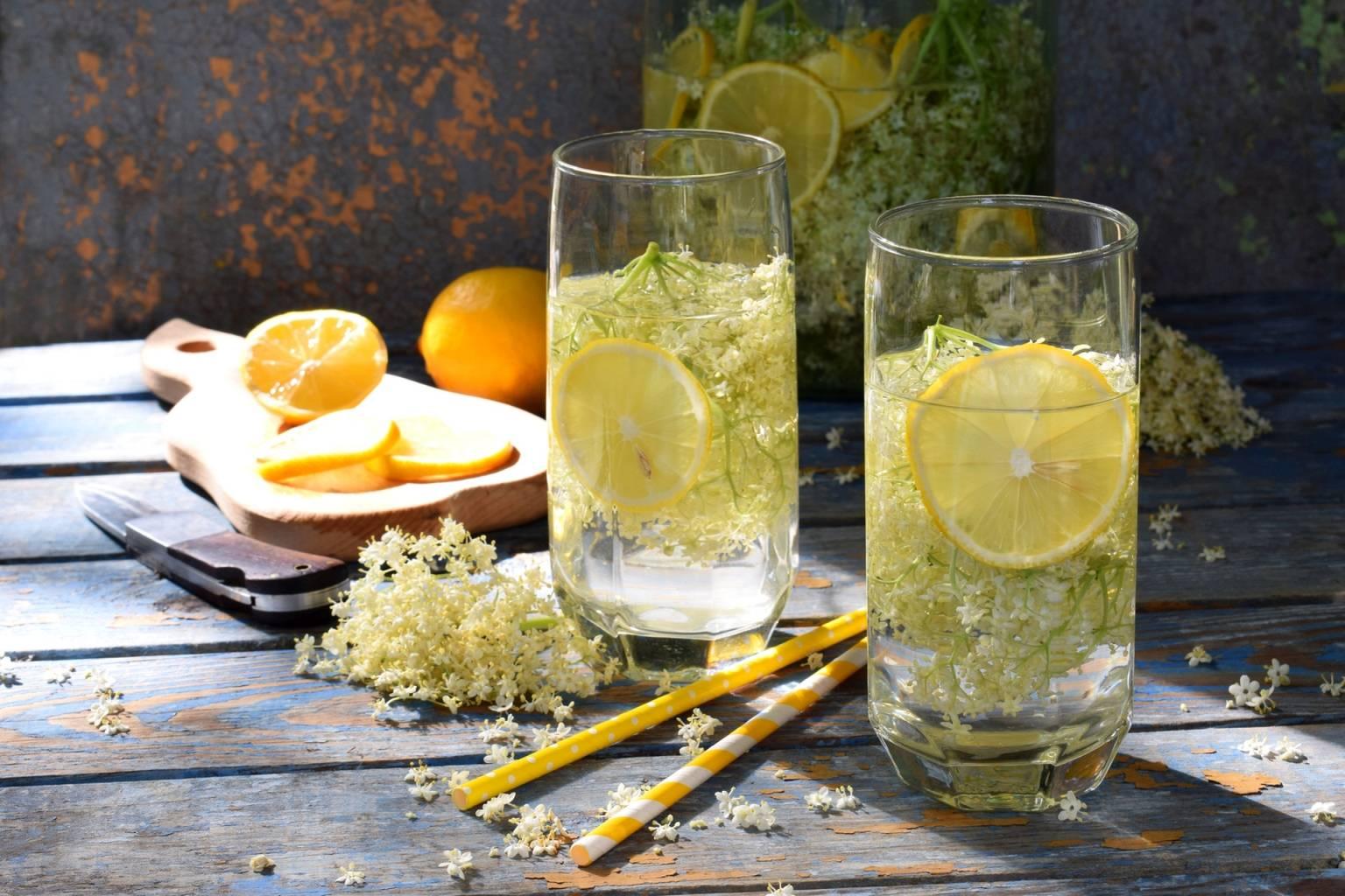 Przepis na odwar z kwiatów czarnego bzu. Na starym drewnianym stole stoją dwie szklanki z wodą z cytryną i kwiatami czarnego bzu. Obok leżą dwie słomki, kwiaty czarnego bzu, deska do krojenia z pomarańczą, w tle stoi słój z napojem z czarnego bzu.