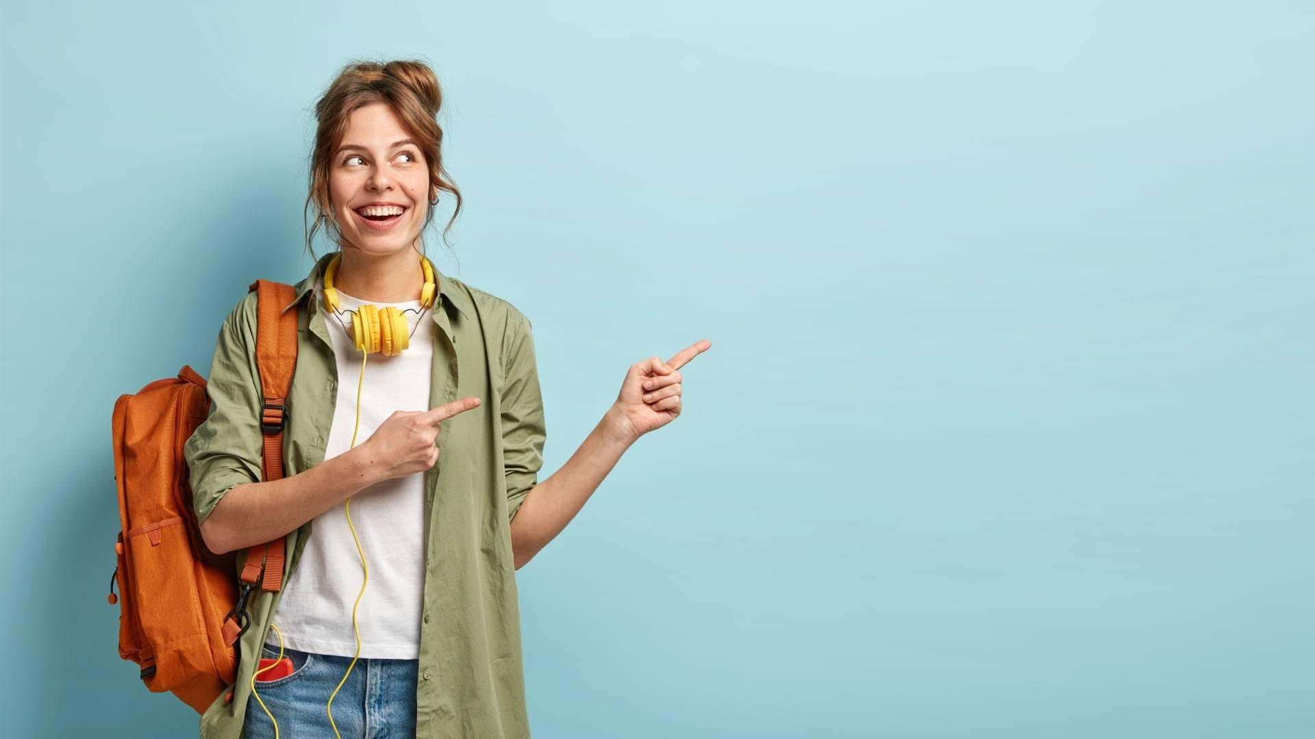 Uśmiechnięta nastolatka z plecakiem i żółtymi słuchawkami. Leki homeopatyczne dla dzieci w wieku nastoletnim