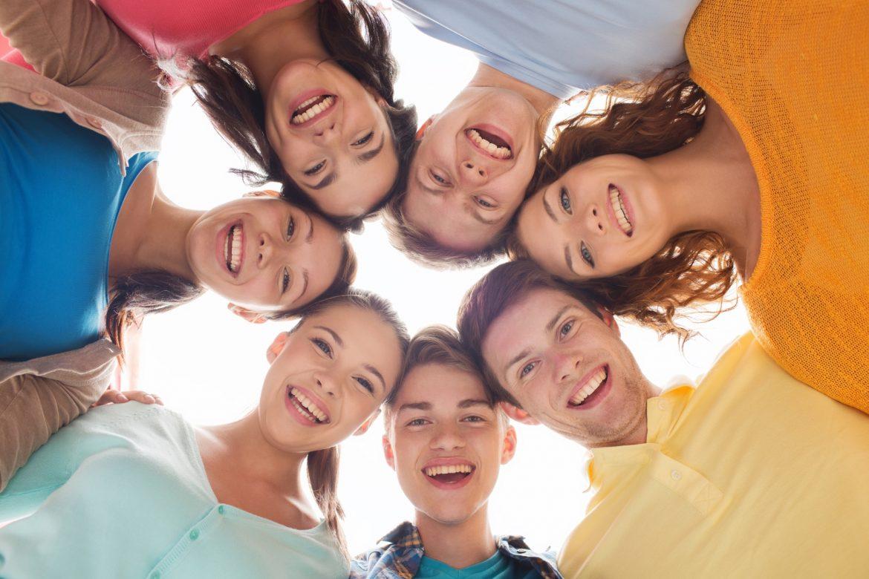 Homeopatia, leki homeopatyczne dla dzieci i dla nastolatków. Grupa uśmiechniętych nastolatków pochyla się w kręgu i patrzy w dół do obiektywu.