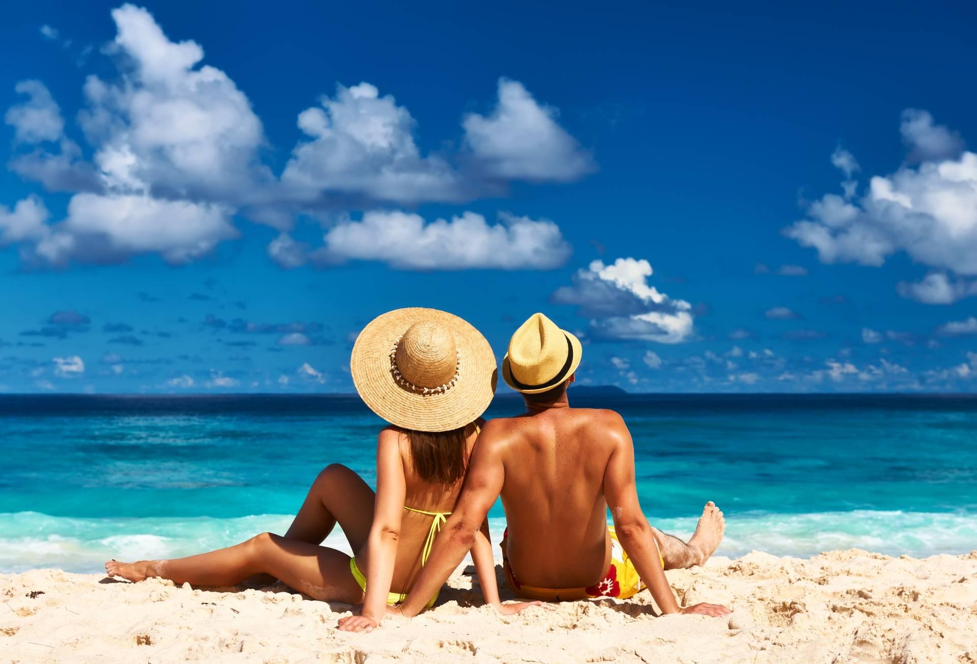 Jak przygotować skórę do opalania? Co jeść i czym smarować skórę? Para siedzi na plaży na tropikalnej wyspie na Seszelach.