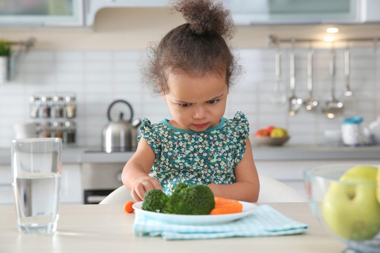 Neofobia żywieniowa - co robić, kiedy dziecko nie chce jeść? Mała dziewczynka podejrzliwie przygląda się warzywom na swoim talerzu.