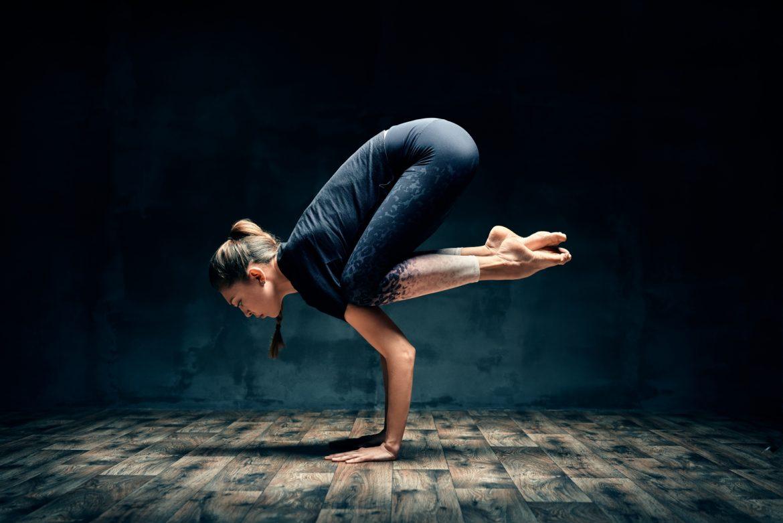 Na czym polega neurojoga? W jaki sposób joga oddziałuje na nasz mózg? Młoda joginka unosi całe ciało, opierając się tylko na rękach.
